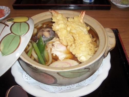 Nabeyaki Udon with shrimp tempura, egg, fishcake, green onions, and ...